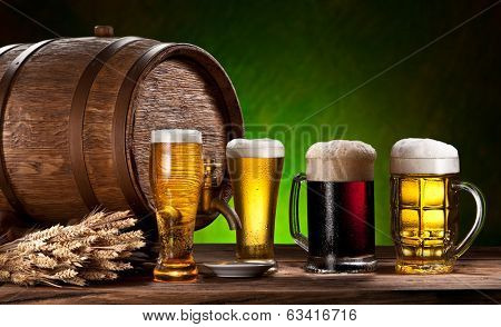 Beer glasses, old oak barrel and wheat on wooden table.