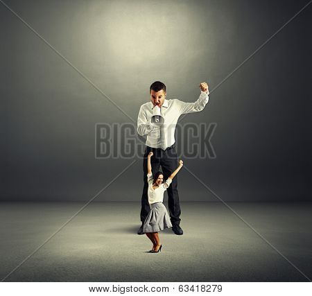 discontented man and merry dancing woman over dark background