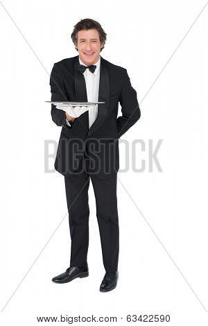 Full length portrait of waiter holding tray over white background