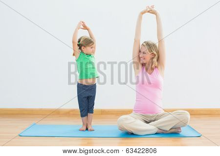 Pregnant smiling mother and daughter doing yoga together in a fitness studio