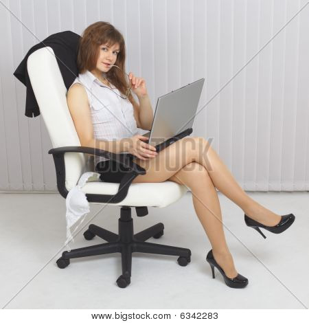 Young Beautiful Sexy Girl Sits In An Armchair With Laptop