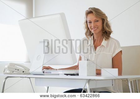 Casual businesswoman smiling at camera at her desk in her office