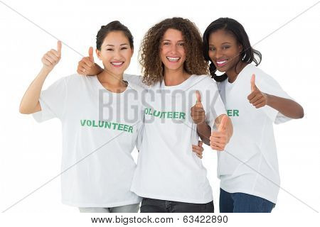 Happy team of volunteers giving thumbs up at camera on white background