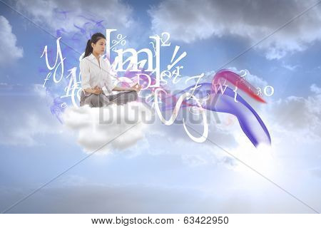 Businesswoman sitting in lotus pose against beautiful orange and blue sky