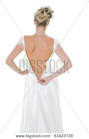Rear view of bride getting dressed over white background