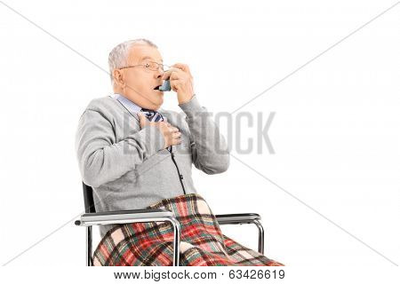 Senior man breathing through his inhaler isolated on white background