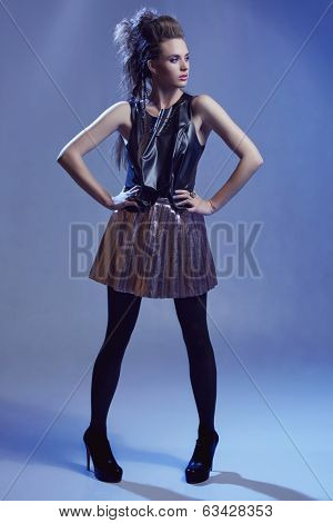 Rocker model girl with long hair in punk hairstyle, wearing black leather top and gold skirt on blue studio background