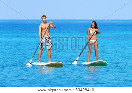 Stand up paddleboarding beach people on stand up paddle board, SUP surfboard surfing in ocean sea on Big Island, Hawaii Beautiful young mixed race Asian woman and Caucasian man doing water sport.