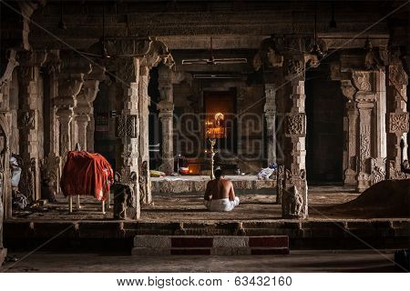 TIRUCHIRAPALLI , INDIA - FEBRUARY 15, 2013:  Unidentified Indian brahmin (traditional Hindu society) priest praying in Hindu temple Tiruchirapalli Rock Fort, Tamil Nadu, India