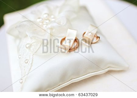 Image of wedding rings on the pillow