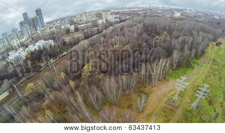 RUSSIA, MOSCOW - OCT 25, 2013: Cityscape with railway passes near the city buildings near the park with power transmission lines, view from unmanned quadrocopter.