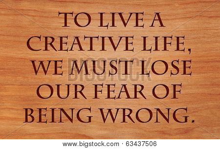 To live a creative life, we must lose our fear of being wrong - quote by unknown author on wooden red oak background