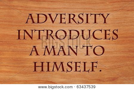 Adversity introduces a man to himself - quote by unknown author on wooden red oak background