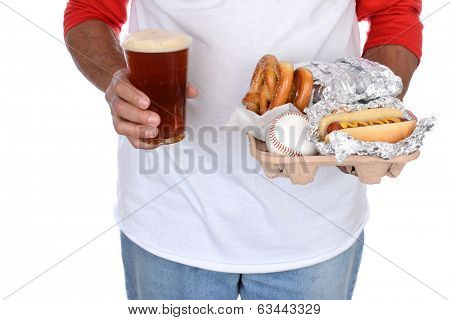 Closeup of a sports fan carrying a tray of food and souvenirs in one hand and a beer in the other. Food tray holds hot dogs and pretzels and a souvenir baseball.