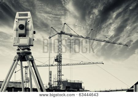 surveyors measuring instrument, close-ups, with construction industry in background
