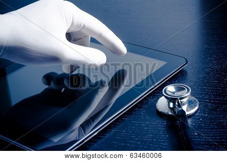 Hand In Medical Glove Touching Modern Digital Tablet Pc Near Stethoscope