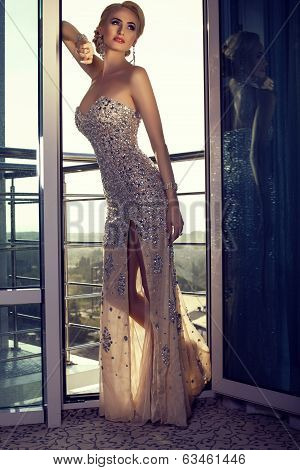 beautiful lady in luxury  dress posing at balcony