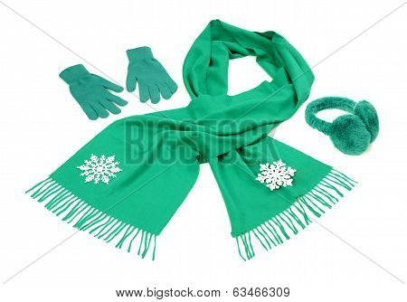 Green wool scarf, a pair of gloves and earmuffs nicely arranged