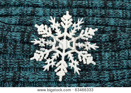Big white snowflake on knitted wool background.