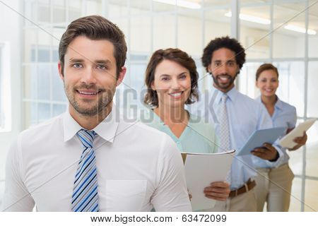 Portrait of business colleagues holding notepads in a row at the office