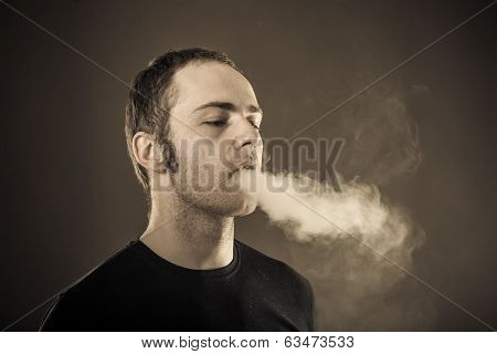 Man exhales smoke.