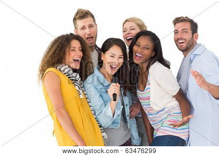 Happy group of young friends having fun doing karaoke on white background