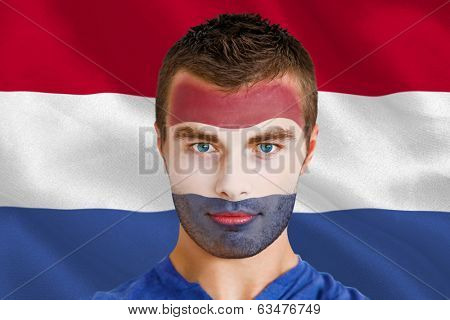 Composite image of serious young netherlands fan with facepaint against digitally generated netherlands national flag