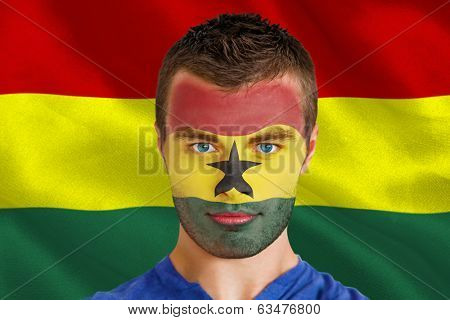 Composite image of serious young ghana fan with facepaint against digitally generated ghana national flag