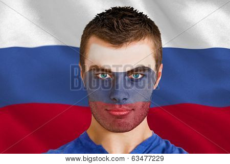 Composite image of serious young russia fan with facepaint against digitally generated russian national flag