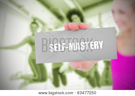 Fit blonde holding card saying self mastery against dance class in gym
