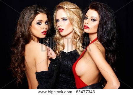 Trio of stunning glamorous women in tantalising evening wear posing close together with pouting sultry sexy looks on a dark background