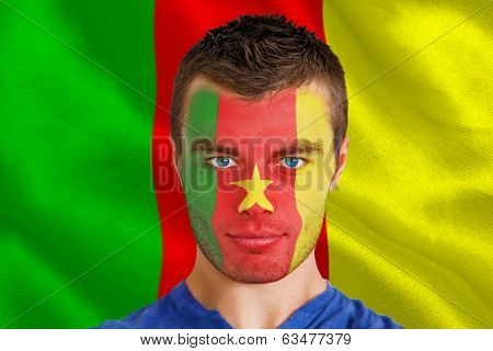 Composite image of serious young cameroon fan with facepaint against digitally generated cameroon national flag