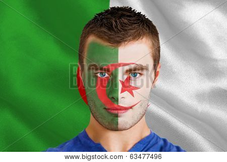 Composite image of serious young algeria fan with facepaint against algerian flag