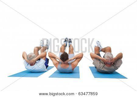 Full length of three men doing abdominal crunches over white background