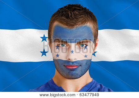 Composite image of serious young honduras fan with facepaint against digitally generated honduras national flag