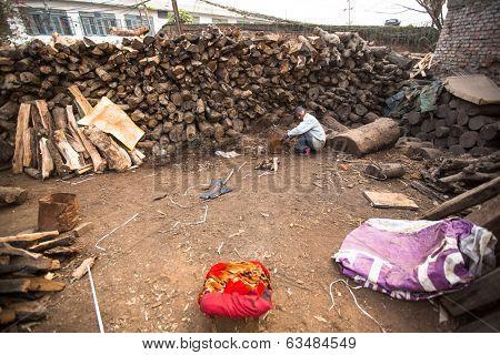 KATHMANDU, NEPAL - DEC 19, 2013: Unidentified man sorts wood for cremation rites in Bhasmeshvar Ghat at Pashupatinath temple in Kathmandu.