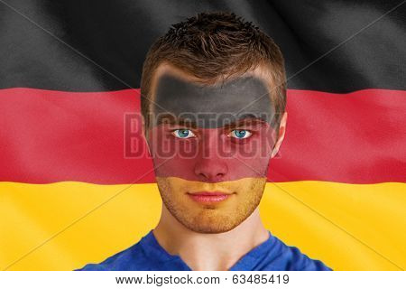 Composite image of serious young belgium fan with facepaint against digitally generated german national flag