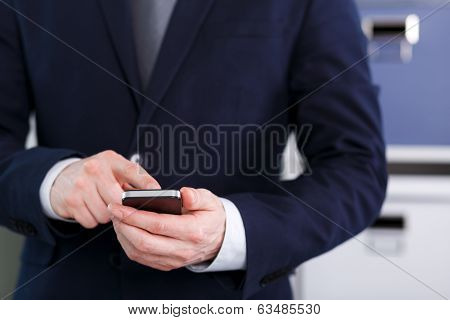 Male Hand Holding A Cell Phone And Writing