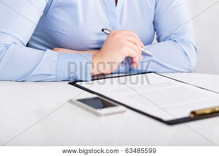 Young Woman Reads A Signed Contract