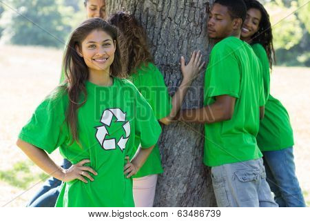 Portrait of female environmentalist at park with friends hugging tree in background