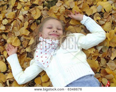 Little girl lying on autumn leaves
