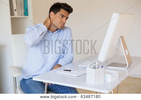 Casual businessman touching his sore neck in his office