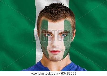 Composite image of serious young nigeria fan with facepaint against digitally generated nigerian national flag