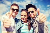 summer holidays and teenage concept - group of smiling teenagers showing thumbs up