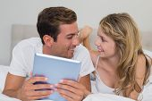 Smiling relaxed young cSmiling relaxed young couple using digital tablet in bed at homeouple using d