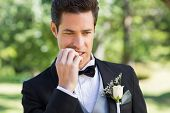 Closeup of young groom biting nails in garden