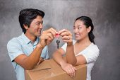 Happy couple holding house key and leaning on moving box in their new home