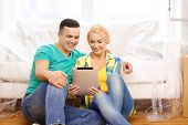 moving, home, technology and couple concept - smiling couple sitting on the floor with tablet pc com