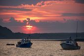 picture of lobster boat  - The sun is setting behind two boats on the Bay of Fundy - JPG