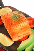 healthy sea food: grilled salmon on iron pan over wooden plate with lemon avocado and tomatoes isola